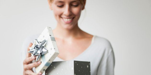 Young woman opening gift box