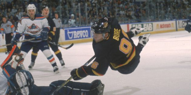 Russian hockey player Pavel Bure of the Vancouver Canucks sails through the air as he tries to score...