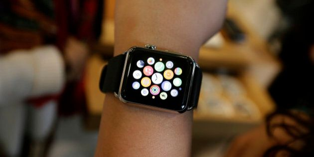 A person poses with an Apple Watch for a picture in a store on Oxford Street in London, Friday, April 10, 2015. The technology company's latest product is on display in the store ahead of its full release for sale on April 24. (AP Photo/Tim Ireland)