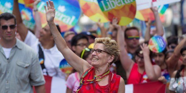 Ontario Premier Kathleen Wynne , the first openly gay premier of Ontario, waves as she marches in the...