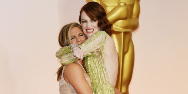 HOLLYWOOD, CA - FEBRUARY 22: Actresses Jennifer Aniston (L) and Emma Stone attend the 87th Annual Academy Awards at Hollywood & Highland Center on February 22, 2015 in Hollywood, California. (Photo by Jason Merritt/Getty Images)