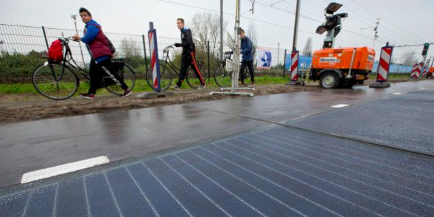 Bicyclists are forced to use the sidewalk as they pass a stretch of bicycle path where a solar panel...