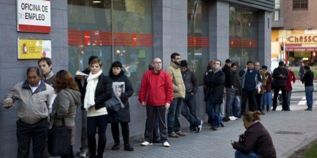 People wait in line at a government employment office on Paseo de las Acacias in Madrid on December 2,...
