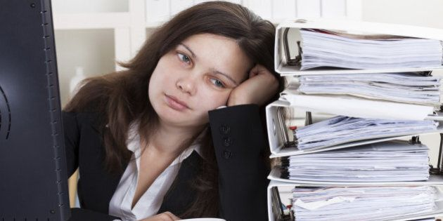 Stressed Businesswoman Working In Office With Stack Of
