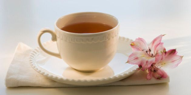 Cup of tea on cloth with flower