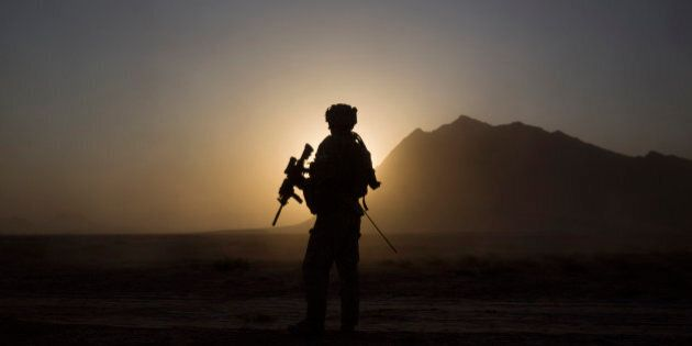 A soldier with the Canadian Army's 1st Battalion 22nd Royal Regiment prepares for an operation at sunrise...