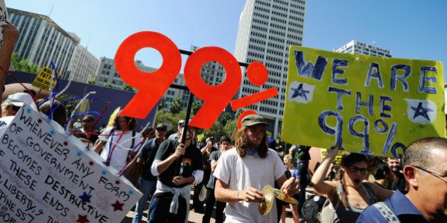 LOS ANGELES, CA - OCTOBER 01:  Protesters hold signs as they march to Los Angeles City Hall during the 'Occupy Los Angeles' demonstration in solidarity with the ongoing 'Occupy Wall Street' protest in New York City on October 1, 2011 in Los Angeles, California. The protesters slogan, 'We are the 99 percent,' calls attention to the fact that marchers are not part of the 1 percent of Americans who hold a vast portion of the nation's wealth.  (Photo by Kevork Djansezian/Getty Images)