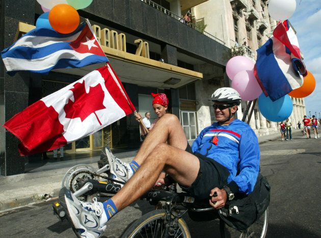 A father and his daughter ride through Prado Boulevard while participating in the 7th Terry Fox Marathon of Hope, in Havana, Feb. 8, 2004.