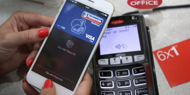 LONDON, ENGLAND - JULY 14: In this photo illustration, an iPhone is used to make an Apple Pay purchase...