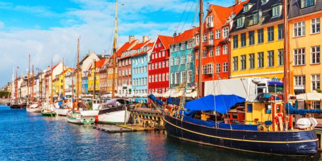Scenic summer view of Nyhavn pier with color buildings, ships, yachts and other boats in the Old Town of Copenhagen, Denmark