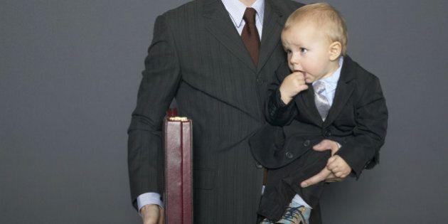 Businessman holding baby son (18-24 months) and briefcase under