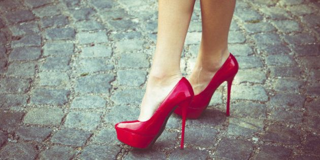 woman legs in red high heel shoes outdoor shot on cobble