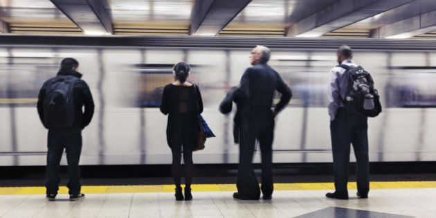 People standing on a platform, waiting for a subway train to arrive. Toronto TTC, Ontario,