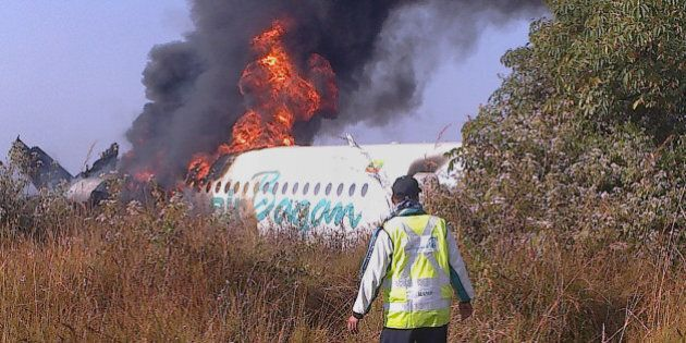 This photo taken on December 25, 2012 shows a man walking the fuselage of an Air Bagan passenger plane burn after it crashed near Heho airport in Myanmar's eastern Shan state. The Myanmar ageing Fokker-100 plane carrying 65 passengers including foreign tourists crash-landed in eastern Shan state, leaving two people dead and 11 others injured, the airline and officials said.   AFP PHOTO        (Photo credit should read STR/AFP/Getty Images)