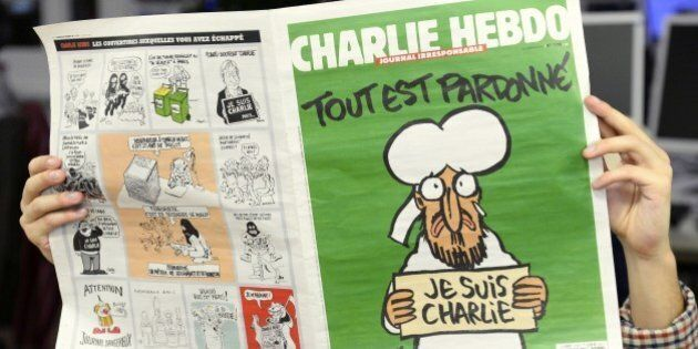 A man reads, in a newsroom in Paris, the last issue of French satirical weekly Charlie on January 13,...
