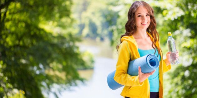 Young beautiful woman holding a yoga mat and water bottle. Healthy lifestyle concept.