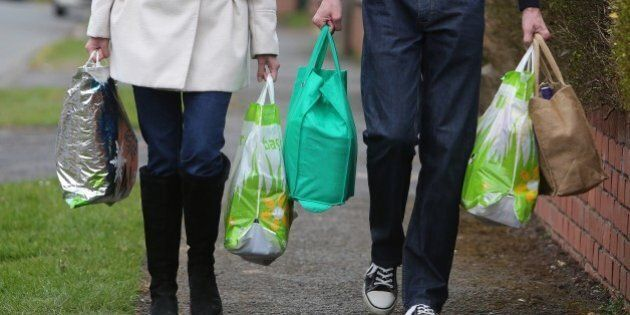 TO GO WITH AFP STORY BY PATRICE NOVOTNYA couple carry their shopping home in bags in Worcester, central...