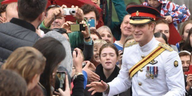 Britain's Prince Harry (C) braves the rain to shake hands with onlookers after laying a wreath at the...