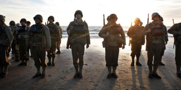 A group of military enthusiasts stand on Omaha Beach in Vierville sur Mer, western France , Friday June...