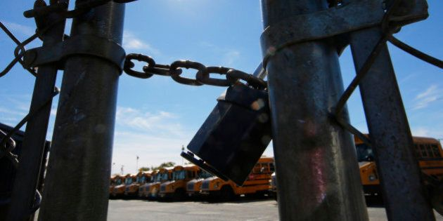The gates of a school bus yard are locked after drivers walked off the job in the morning in Boston,...