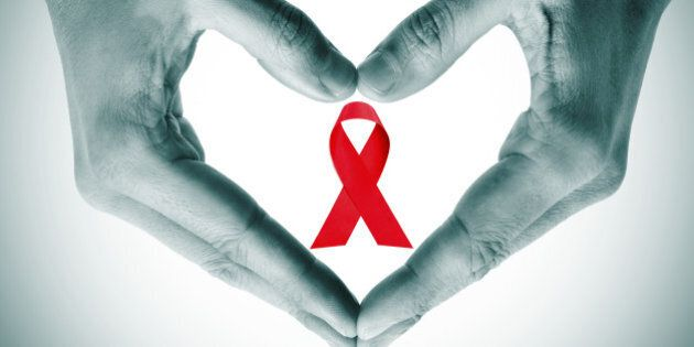 man hands forming a heart with his hands and a red ribbon for the fight against AIDS on a white
