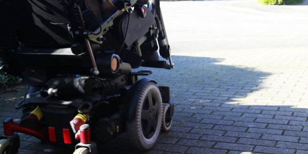 side view of disabled man driving an electric wheelchair