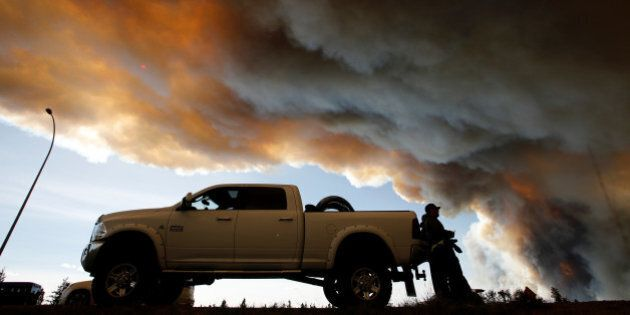 People wait at a roadblock as smoke rises from wildfires near Fort McMurray, Alberta, Canada, May 6,...