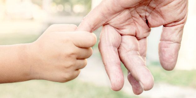 Young child holding her grandparent for the hand,selective