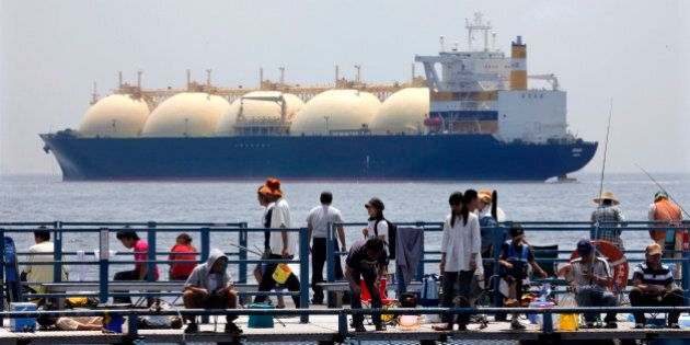 JAPAN - JUNE 20: A liquefied-natural-gas (LNG) tanker, leaves a berth as holidaymakers fish on a pier...