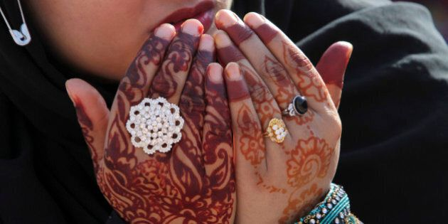 A Pakistani worshipper wearing henna designs on her hands prays at the Badshahi Mosque on the first day...