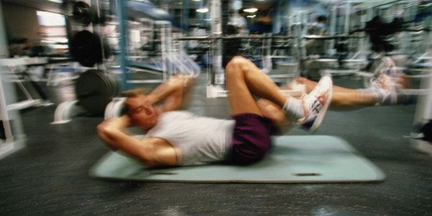 Man exercising in gym (blurred motion)