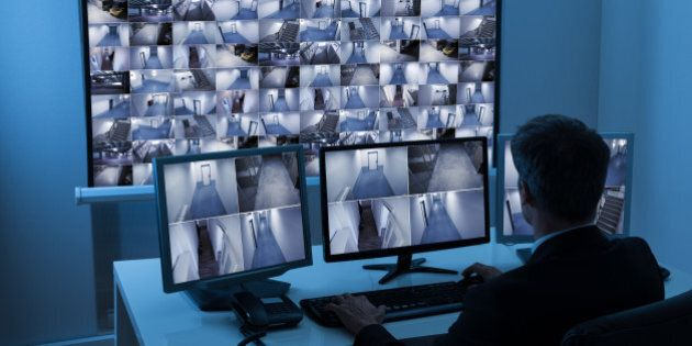 Rear View Of A Man In Control Room Monitoring Multiple Cctv