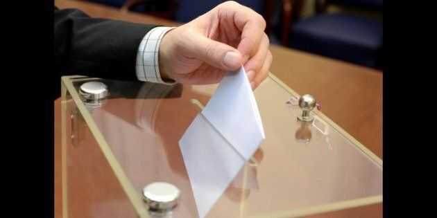 ballot box and hand putting a blank ballot inside, elections and democracy