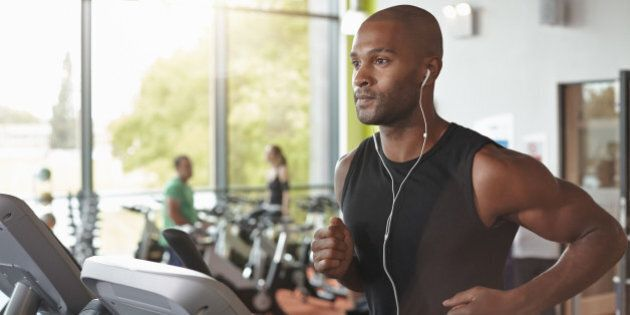 Man in a gym running on a treadmill with head phones in.