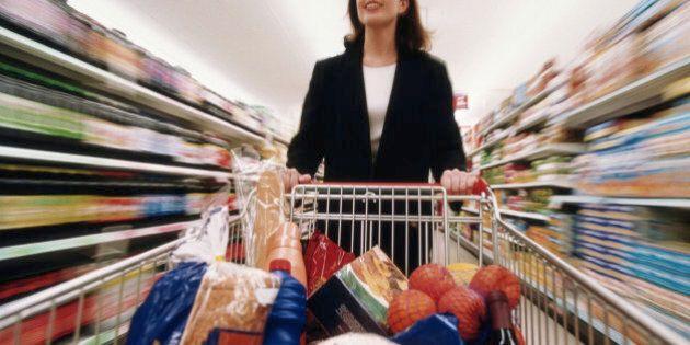 BUSINESSWOMAN PUSHING TROLLEY ROUND SUPERMARKET