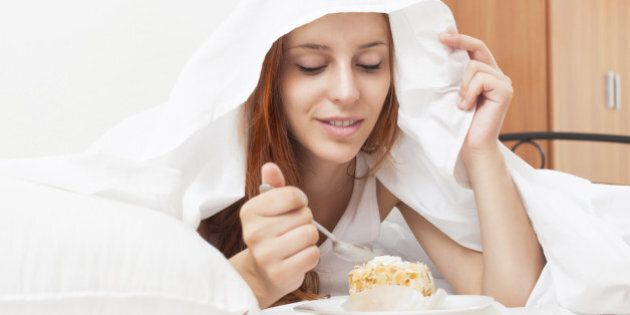 Long-haired young woman eating sweet cake under white sheet in bed at
