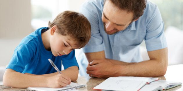 Portrait of a happy man helping his son to do homework -
