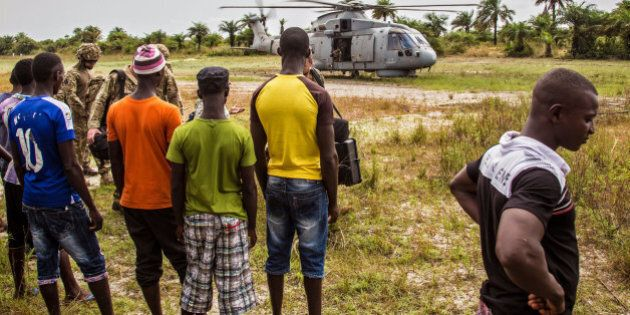 Local residents look at a British Navy helicopter after it made a food drop on Sherbro Island, Sierra...