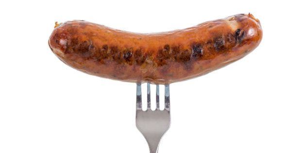 Grilled Sausage on a fork isolated on white