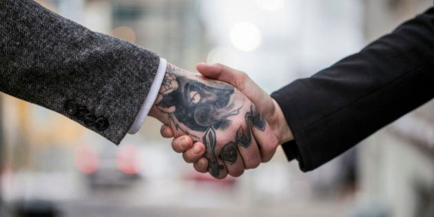 A cropped photo of business colleagues shaking hands outdoors. Tattooed businessman greeting female colleague....