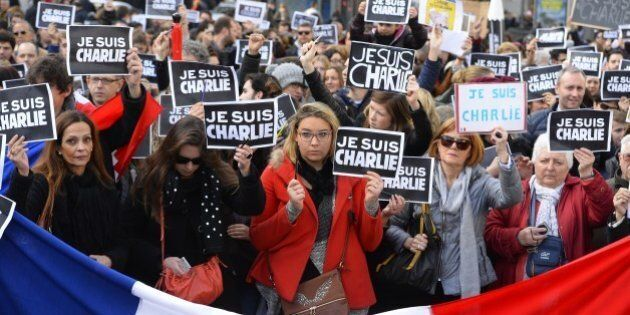 People hold placards reading in French 'I am Charlie' behind a french flag during a public show of solidarity...
