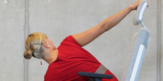 yoga on chair in office - business woman exercising, back
