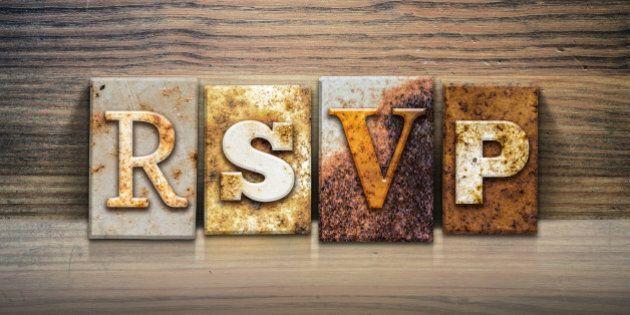 The word 'RSVP' written in rusty metal letterpress type sitting on a wooden ledge background.