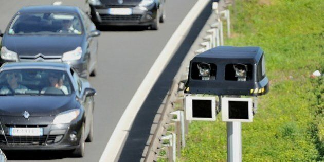 Motorists drive by a radar part of an average speed measuring system, on June 23, 2014 near Englos, northern...