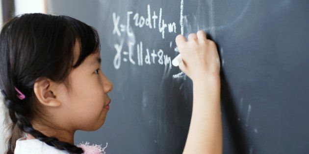Girl writing on blackboard in