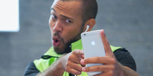 A customer, right, takes a 'selfie' photograph with an iPhone 6 Plus during the sales launch of the latest...