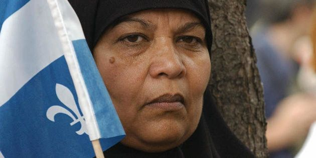 A Pakistani woman holds a Quebec flag during a demonstration called 'No One is Illegal' against the World...