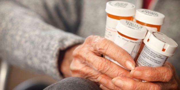 Senior citizen female holding bottles of prescription medicine sitting in a