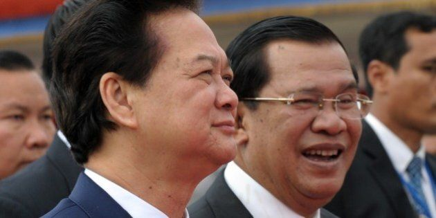 Vietnamese Prime Minister Nguyen Tan Dung (L) walks with Cambodian Prime Minister Hun Sen (R) during...
