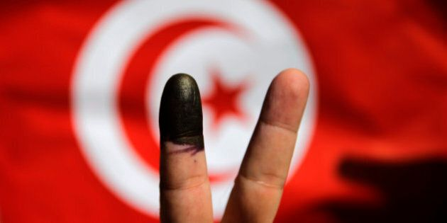 A Tunisian man shows his ink-stained finger in front of a Tunisian flag after voting for the country's...